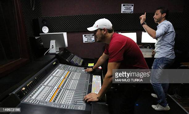 Libyan technicians work at the studio of Radio Zone one of the hippest channels to hit the airwaves since the ouster of Moamer Kadhafi on August 5...