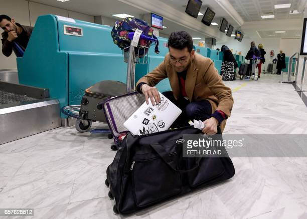 A Libyan traveller packs his laptop in his suitcase before boarding his flight for London at TunisCarthage International Airport on March 25 2017 The...