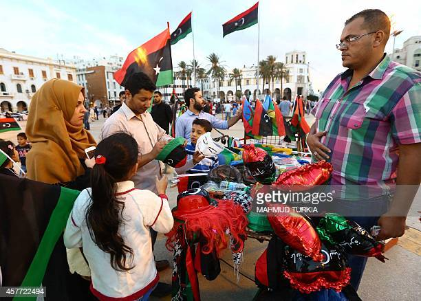 A Libyan vendor sells items displaying the national flag during celebrations for the third anniversary of the 2011 Libyan revolt in Tripoli on...