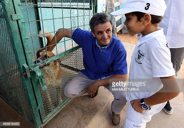 Libyan vet Jalal Kaal shows a dog he rescued to a child at his clinic in the Libyan capital Tripoli on October 19 2015 When evacuated foreigners left...