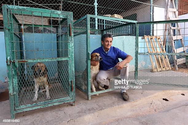 Libyan vet Jalal Kaal strokes a dog he rescued in Tripoli at his clinic in the Libyan capital on October 19 2015 When evacuated foreigners left their...