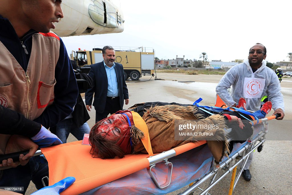 A Libyan volunteer is carried by medical staff during a drill simulating a plane crash organized by the International Committee of the Red Cross in cooperation with the Libyan Red Crescent, for training on disaster management at Mitiga Airport on December 12, 2012 in Tripoli.