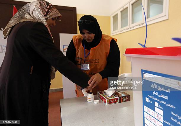 A Libyan woman dips her finger in indelible ink after voting to elect a constituent assembly at a polling station in the capital Tripoli on February...