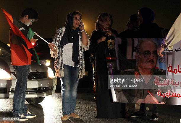 A Libyan woman holds a picture of MajorGeneral Halifa Haftar as people celebrate the decision by their parliament to reject the UN proposals for a...