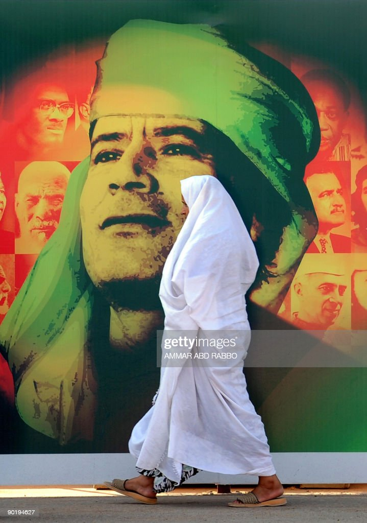 A Libyan woman walks past a picture of Libyan leader Moamer Kadhafi in Tripoli on August 30, 2009 as celebration to mark the 40th anniversary of Kadhafi coming to power get under way. Libya is marking on September 1 the anniversary of the coup against the monarchy that brought Kadhafi to power on September 1, 1969.