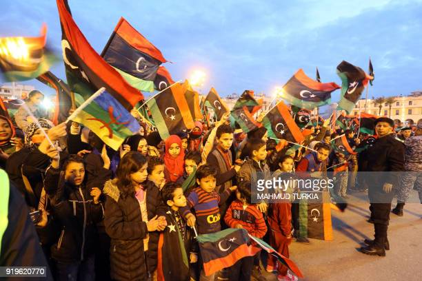 A Libyan woman waves an Amazigh flag while others wave their national flag during a celebration marking the seventh anniversary of the Libyan...