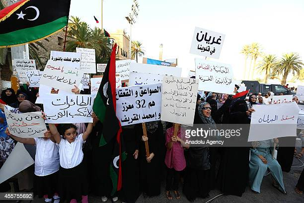 Libyan women hold placards during a demonstration held in the Martyrs' Square where thousands of people gathered to protest the House of...