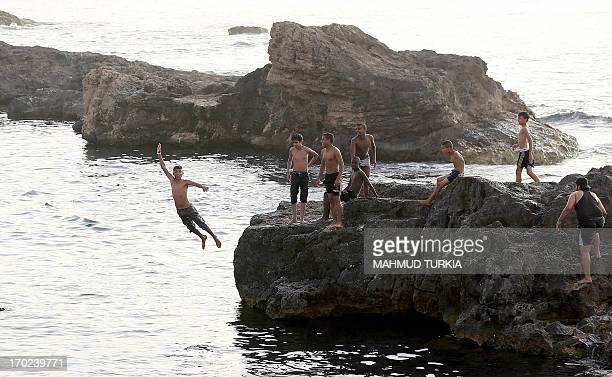 Libyan youth cool off at the seaside with the onset of summer and high temperatures in the Libyan capital Tripoli on June 9 2013 AFP PHOTO/MAHMUD...