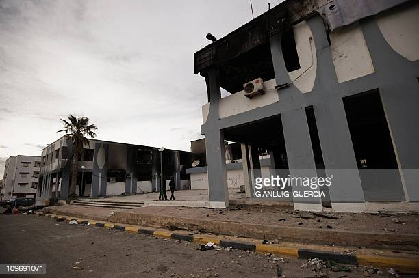 Libyan youths walk past a torched government building in the eastern Libyan town of Derna between Tobruk and Benghazi on February 23 2011 amid...