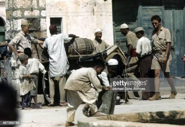 Libyanese men load a cart with barrels as military men watch in Benghazi Libya