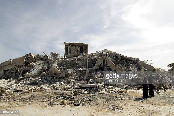 Libyans arrive to inspect on November 1 the rubble of the destroyed 'Beit alSamed' or 'The Resisting House' as dubbed by slain Libyan leader Moamer...