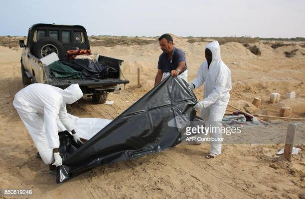 Libyans bury the bodies of migrants that drowned in a shipwreck off the coast of Sabrata at a grave site in Zouara on September 21 2017 At least...