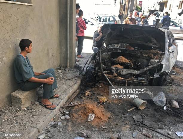 Libyans check a street in the capital Tripoli on April 17, 2019 in the aftermath of several rocket attacks the previous night. - A number of rockets...