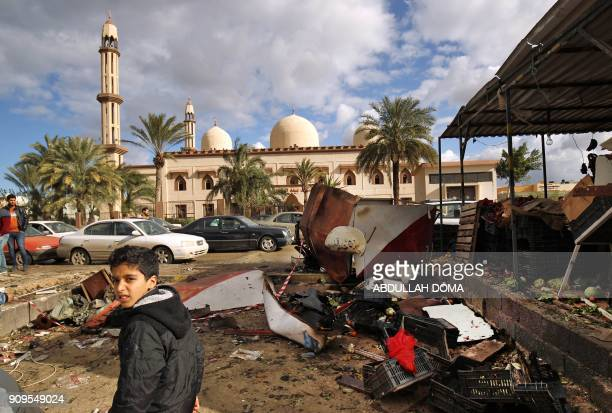 TOPSHOT Libyans check the aftermath of an explosion in the eastern city of Benghazi on January 24 2018 The death toll following a double car bomb...