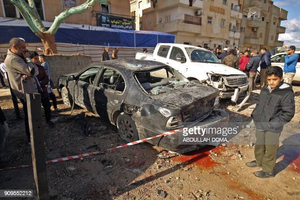 Libyans check the aftermath of an explosion in the eastern city of Benghazi on January 24 2018 The death toll following a double car bomb attack in...