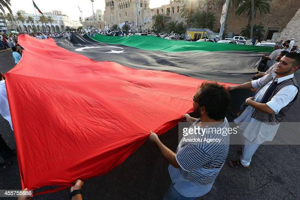 Libyans hold a big flag of Libya during a demonstration held in the Martyrs' Square where thousands of people gathered to protest the House of...