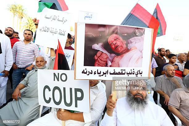 Libyans hold placards one reading in Arabic Why are the innocent of Derna being shelled during a protest against the new antiIslamist parliament on...