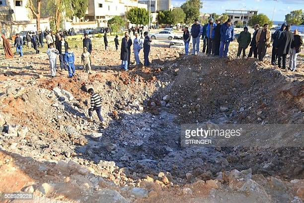 Libyans inspect a crater following a reported air strike that hit a hospital on February 7 in Derna 100 kilometres east of the capital Tripoli...