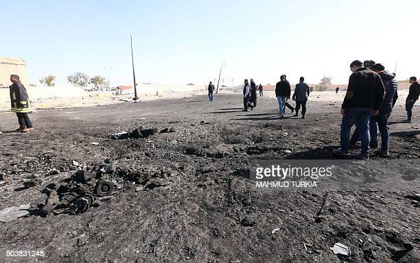 Libyans inspect the site of a suicide truck bombing on a police school in Libya's coastal city of Zliten some 170 kilometres east of the capital...