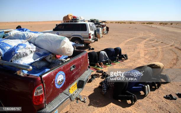 Libyans perform a prayer as they take part in a 4x4 tourism trip in a desert area near al-Shuwayrif town, some 400 Km southwest of the capital, on...