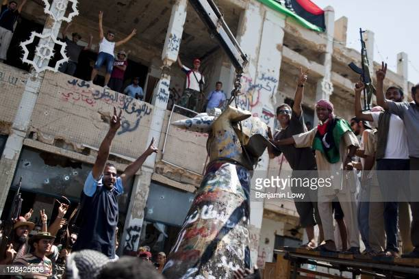 Libyans raise their arms in celebration as they tear down the infamous 'hand crushing a plane' statue in Gaddafi's Bab alAziziyia compound on August...