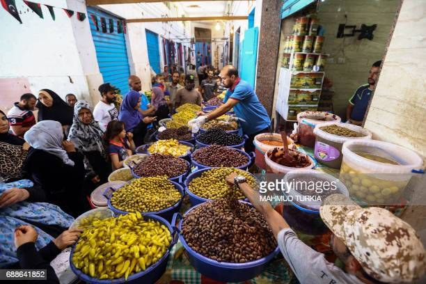 Libyans shop for olives and pickles at a market in the center of the capital Tripoli as the faithful prepare for the start of the Muslim holy fasting...