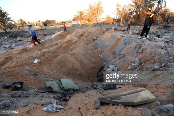 Libyans stand next to a crater and debris at the site of a jihadist training camp targeted in a US air strike near the Libyan city of Sabratha on...