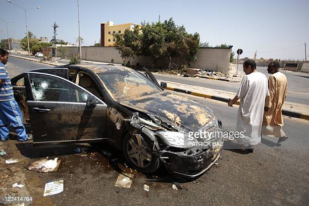 Libyans walks past the destroyed bullet proof car of Libyan former Prime Minister Baghdadi alMahmoudi in Tripoli on August 28 2011 AFP PHOTO/PATRICK...