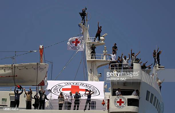 Libyans wave aboard a ferry approaching the rebel stronghold of Benghazi after they were evacuated from Tripoli by the International Committee of the...