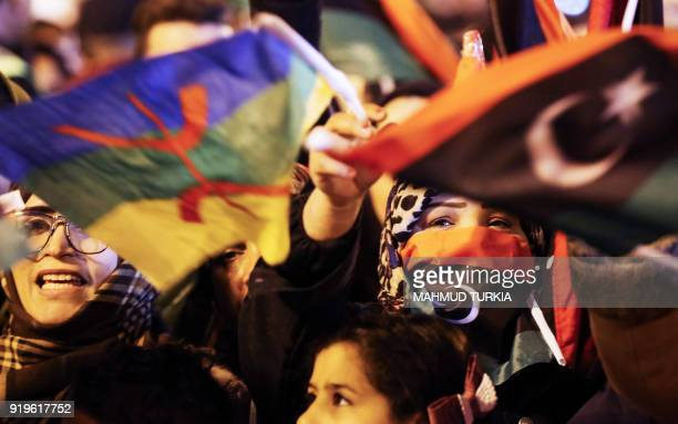 Libyans wave their national flag alongside the Amazigh flag as they attend a celebration marking the seventh anniversary of the Libyan revolution...