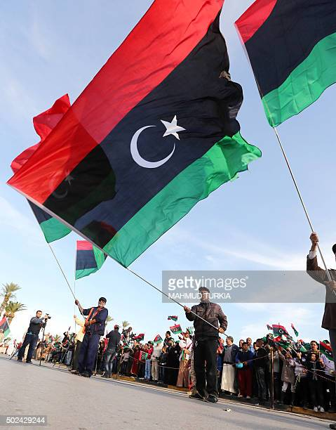 Libyans wave their national flags during a rally to celebrate the country's 64th independence anniversary at the Martyrs square in the capital...