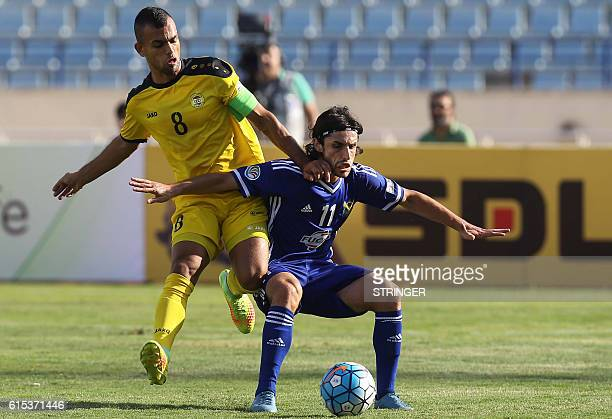 Libya's Hussein Dakik vies for the ball with Iraq's Humam Tareq Faraj during the 2016 Asian Football Confederation Cup semifinal second leg football...