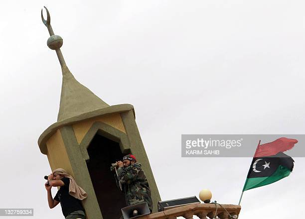 Libya's National Transitional Council fighters scan the area from the minaret of a mosque on the outskirts of the desert city of Bani Walid on...