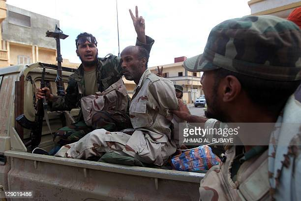 Libya's new regime fighters arrest an alleged Moamer Kadhafi loyalist in the city of Sirte on October 10 2011 during heavy battles in a drive to...