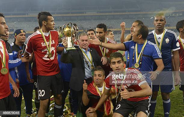 Libya's Spanish coach Javier Clemente celebrate's with his team after beating Ghana on penalty shootouts in Cape Town on February 1 2014 during the...