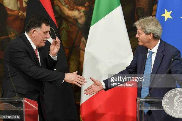 Libya's UN-backed Prime Minister Fayez al-Sarraj and Italian Prime Minister Paolo Gentiloni shake hands at the end of a joint press conference...