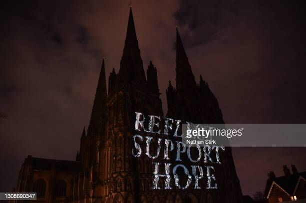 """Lichfield Cathedral is illuminated in yellow with the words, """"Reflect, Support, Hope"""" on National Day of Reflection on March 23, 2021 in Lichfield,..."""
