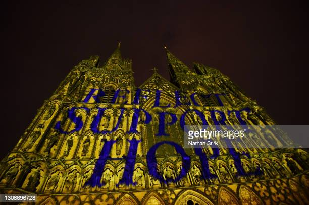 """Lichfield Cathedral is illuminated in yellow with the words, """"Reflect, Support, Hope"""" for a National Day on March 23, 2021 in Lichfield, England...."""
