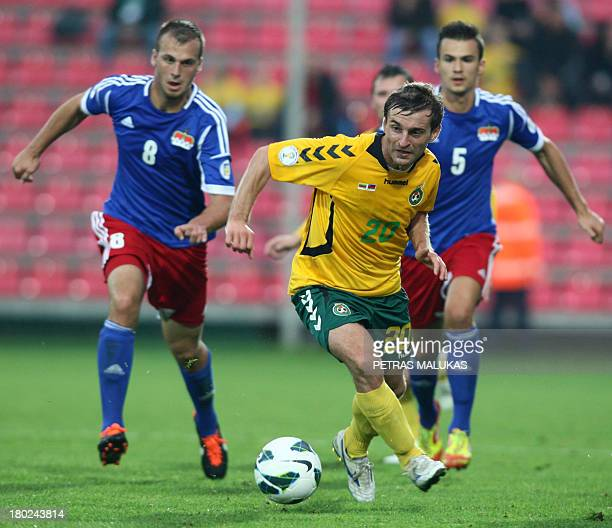 Lichtenstein's Robin Gubser Ivan Qvintans vie for the ball with Lithuania's Mindaugas Kolonas on September 10 2013 during FIFA World Cup 2014...