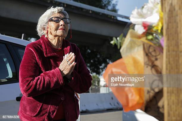 Lidia Marquez prays near the site of a warehouse fire that has claimed the lives of at least twentyfour people on December 4 2016 in Oakland...