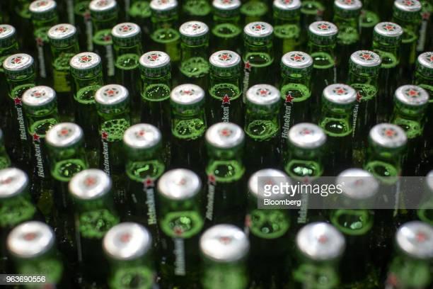 Lids sit on green Heineken beer bottles moving along a conveyor at the Heineken NV brewery in Zoeterwoude Netherlands on Wednesday May 30 2018...