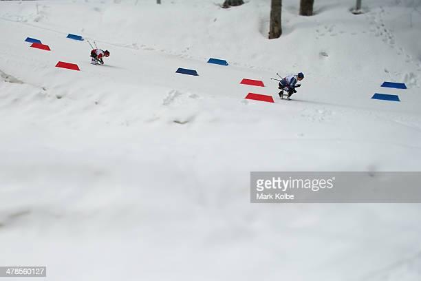 Lidziya Hrafeyeva of Belarus and Marta Zaynullina of Russia compete in the women's 125km sitting biathlon on day seven of the Sochi 2014 Paralympic...