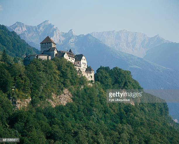 Liechtenstein Vaduz The Castle nestling in wooded hillside rugged mountains behind