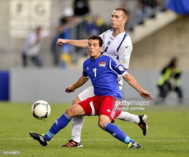 Liechtenstein's David Hasler vies for the ball with BosniaHerzegovina's Toni Sunjic during their FIFA 2014 World Cup qualifying football match...