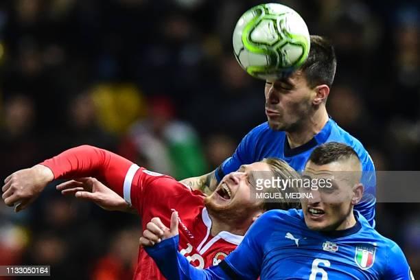 TOPSHOT Liechtenstein's forward Nicolas Hasler Italy's defender Alessio Romagnoli and Italy's midfielder Marco Verratti go for a header during the...