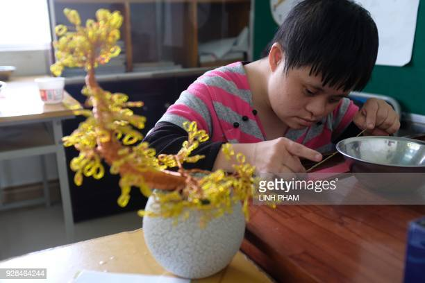 Lieu who suffers the affects of Agent Orange works on a project at a centre for victims of the wartime defoliant during a visit by the crew of USS...