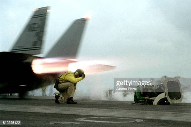 Lieut Michael Stone ends launching signals for an F14 Tomcat taking off from USS Nimitz