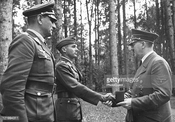 Lieutenant Colonel Dinort left and Major Storp center receive the Oakleaf cluster to the Iron Cross from Adolf Hitler Germany 1941