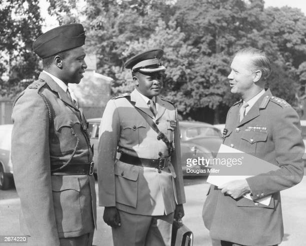 Lieutenant Colonel Idi Amin commanding officer of the Ugandan Rifles talking to officers of the British and Kenyan armies during his visit to Britain...