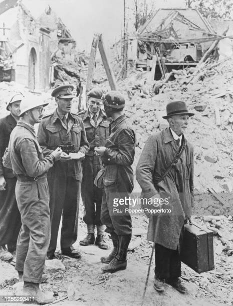 Lieutenant General John Crocker of the British Army General Officer Commanding of I Corps talks with a local resident in the bomb damaged rubble of...